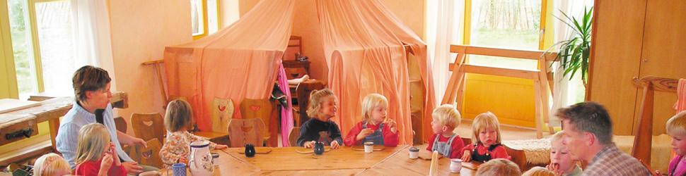 Kinder am Tisch mit Erziehern